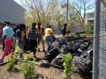 Members of International Youth Organization bagging and collecting debris from site of community garden