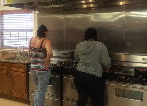Two women prepare dinner for their families at YMCA supportive housing program. In April, they are excited to participate in the healthy nutrition program sponsored by Shaping Elizabeth.