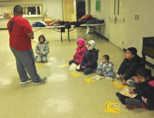 Omar teaching the kids about a healthy plate before they start their fitness fun.