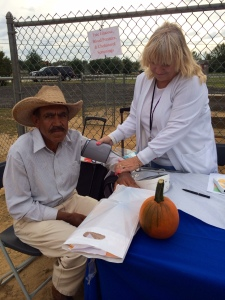 Public Health Nurse Judy MacNeal providing a  preventive health screening to county resident Miguel Rodriguez.